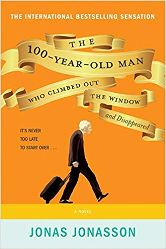 Mustard-yellow cover with an old man with white hair who is stooped over, wearing all black and pulling a black suitcase.