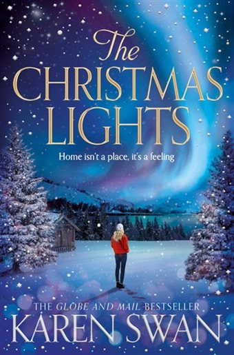 The northern lights light up the sky, mountains and blue waters. A blond woman wearing a red coat stands and looks at the view. It's snowing and there are snow-covered pine trees around her.