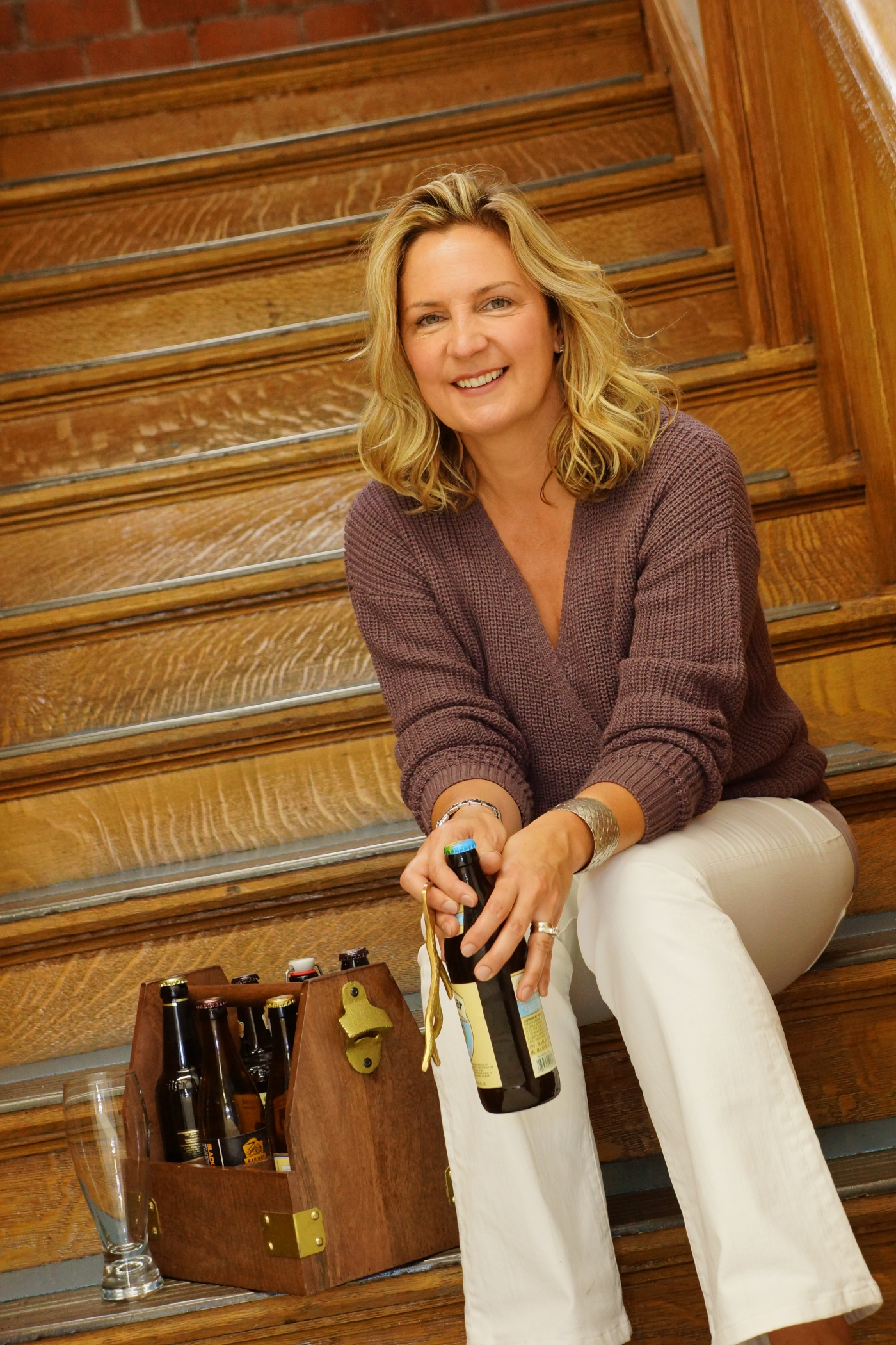 Tonia Wislon sits on honey oak stairs with a bottle of beer in her hand and a wood case filled with other bottles of beer and an empty beer stein.
